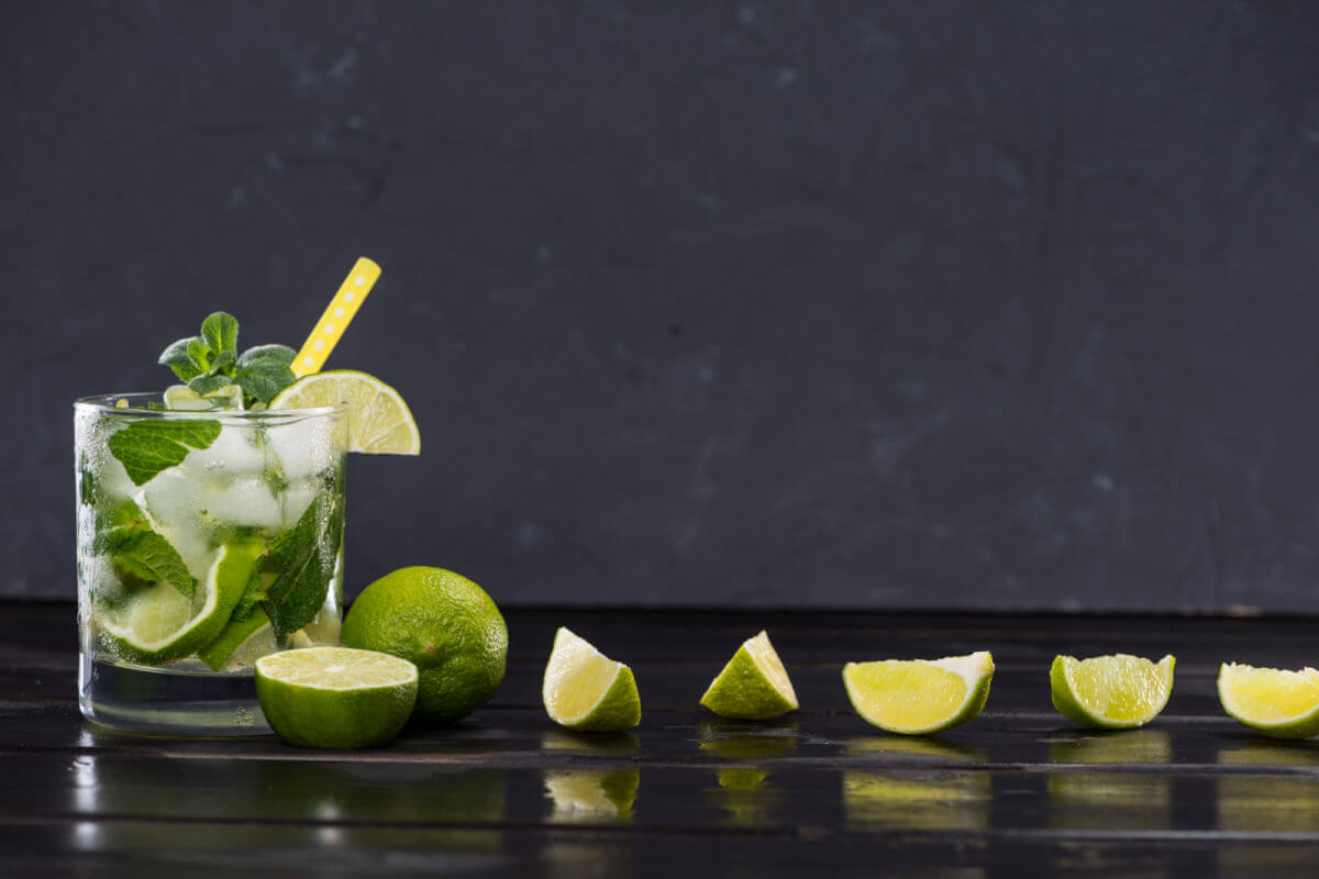 Classic mojito cocktail with lime wedges on a black slate tray