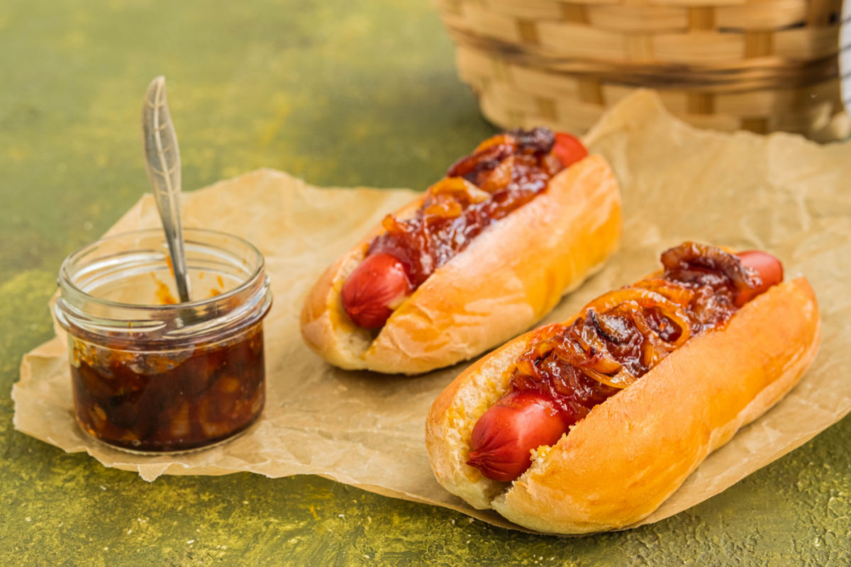 2 NYC-style Dirty Water Dogs with onion sauce on brown paper with a jar of onion sauce on the side