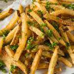 Parmesan Truffle Fries on white paper, garnished with fresh parsley.