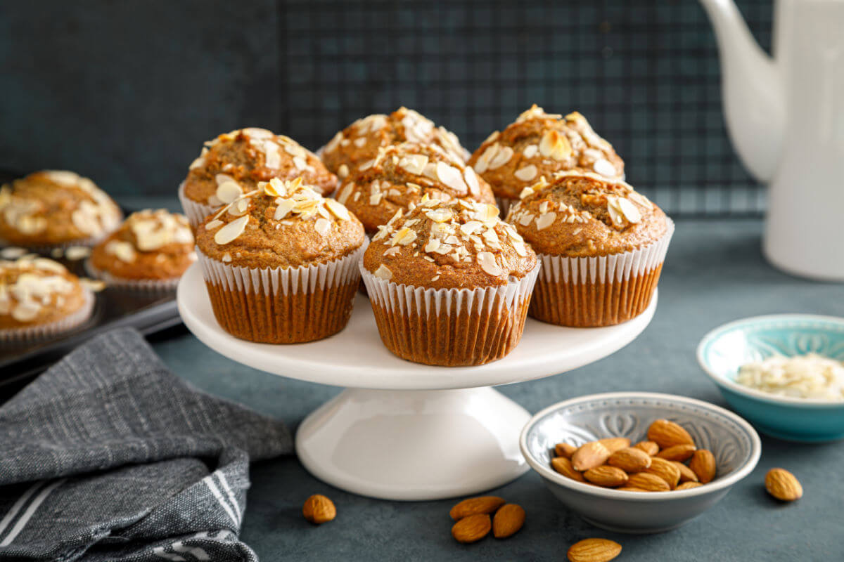 Platter of Bakery-style Almond muffins with an amaretto syrup glaze and sliced almonds on top.