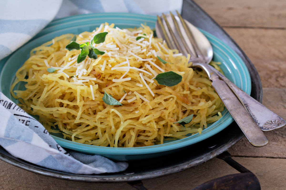 Blue bowl with a serving of brown butter garlic parmesan spaghetti squash and garnished with fresh sage leaves.