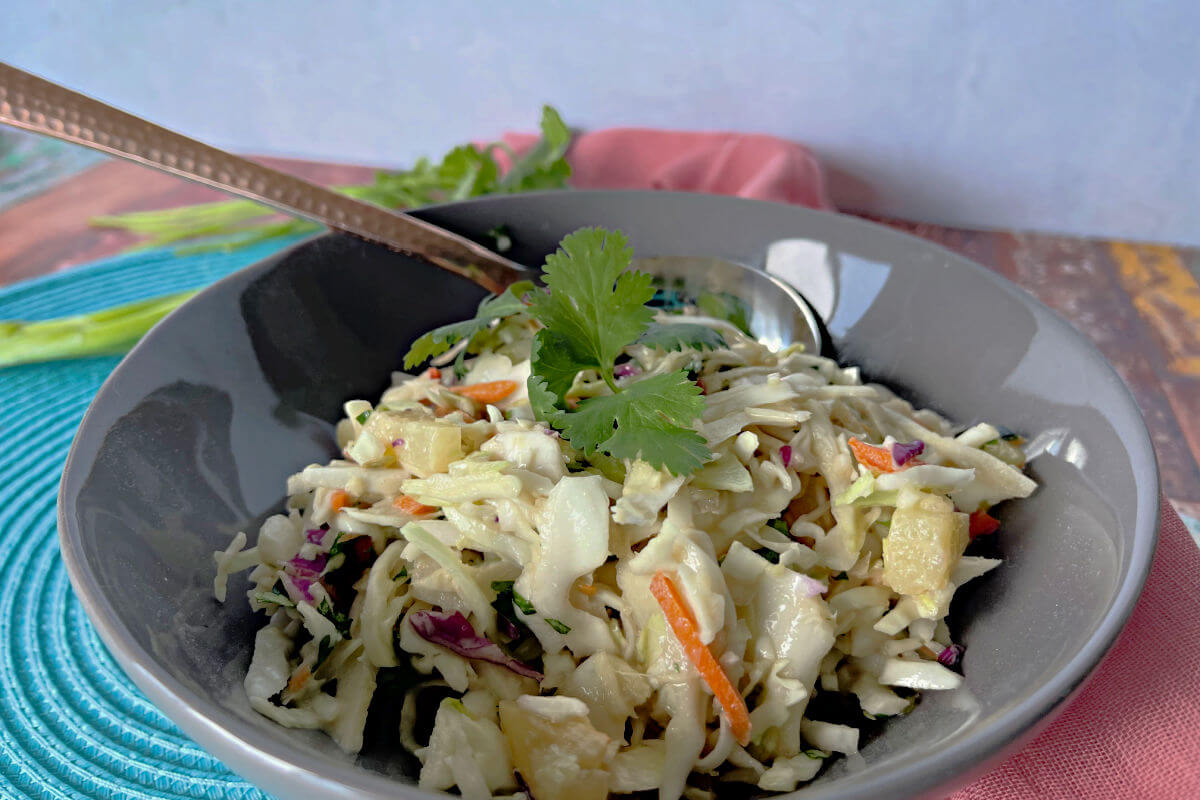 Gray bowl full of crunchy, sweet tropical slaw - cabbage, carrots, jalapeno, scallions, and cilantro in a sweet and sour yogurt dressing.