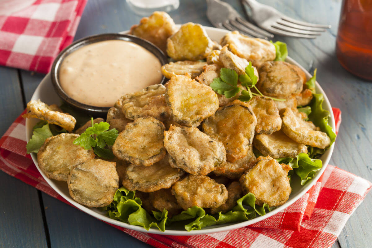 Plate of ridiculously good fried pickles with a side of sauce for dipping.