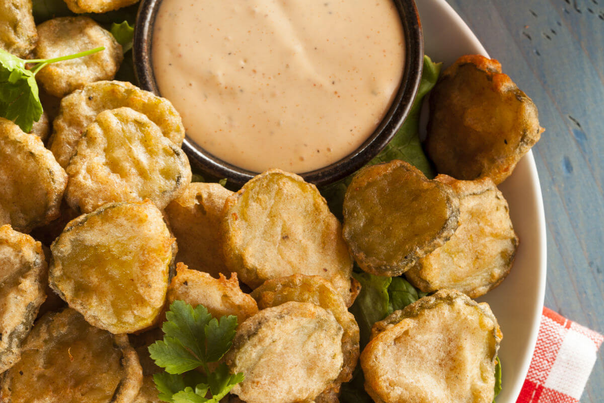Plate of ridiculously good fried pickles with a side of dipping sauce