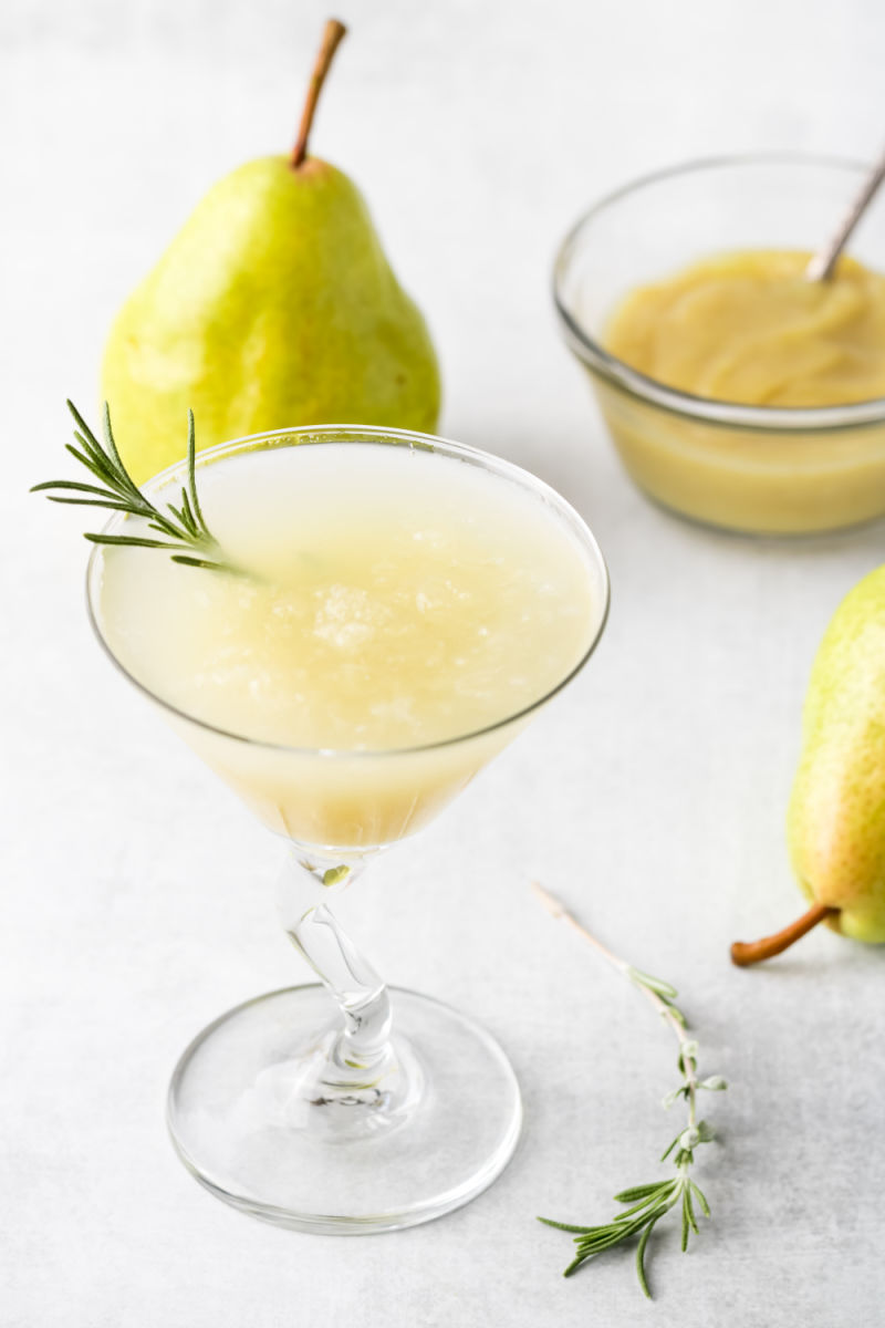 Martini glass with sparkling rosemary pear martini garnished with a sprig of rosemary