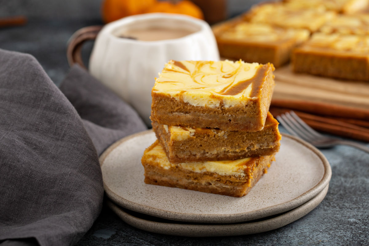Wooden board with squares of Pumpkin Cheesecake Bars - gingersnap crust and swirls of spiced pumpkin and cheesecake.