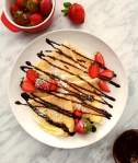 3 crepes folded into triangles on plate with strawberries, chocolate sauce and powdered sugar