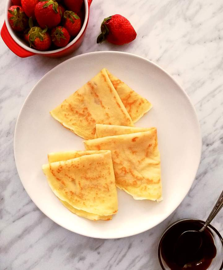 3 crepes folded into triangles on plate