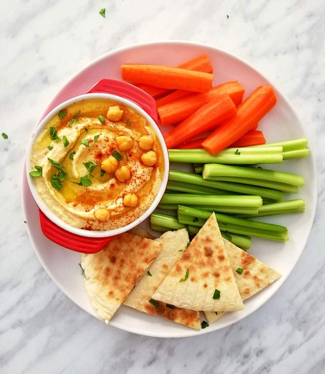 hummus in bowl with carrots, celery, and pita bread