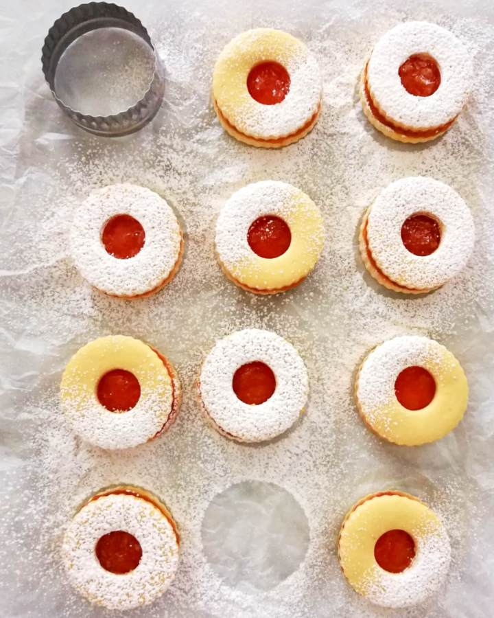 apricot jam filled sandwich cookies laid out on parchment paper overhead image