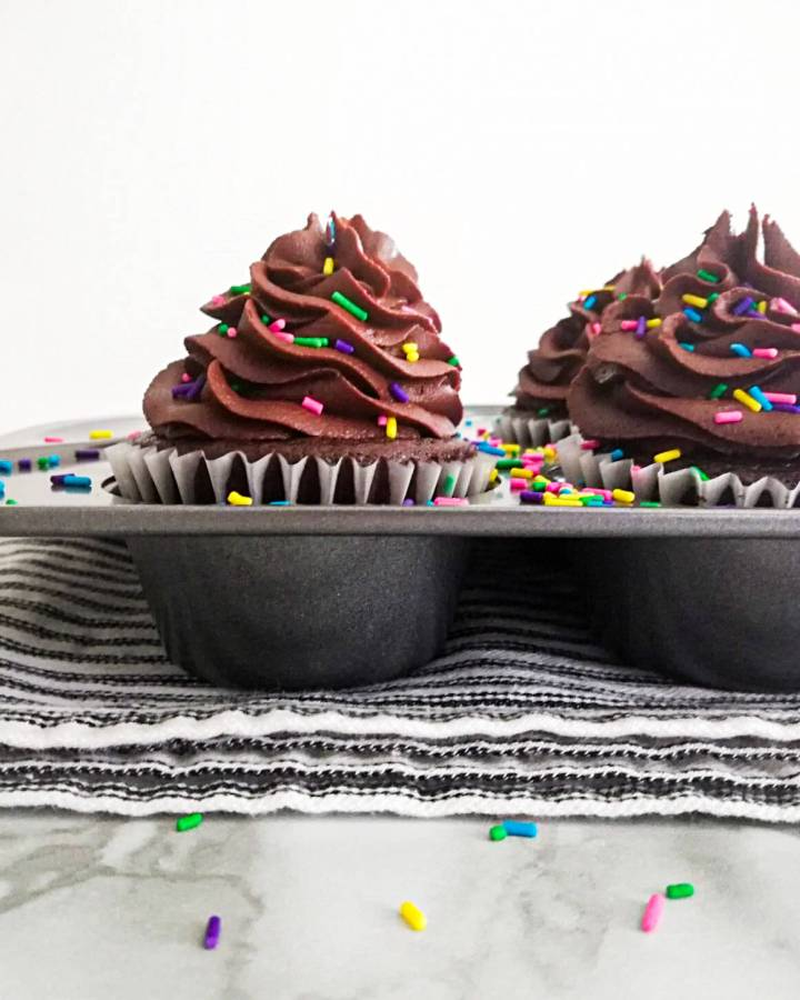 chocolate cupcakes frosted and topped with sprinkles in cupcake tin