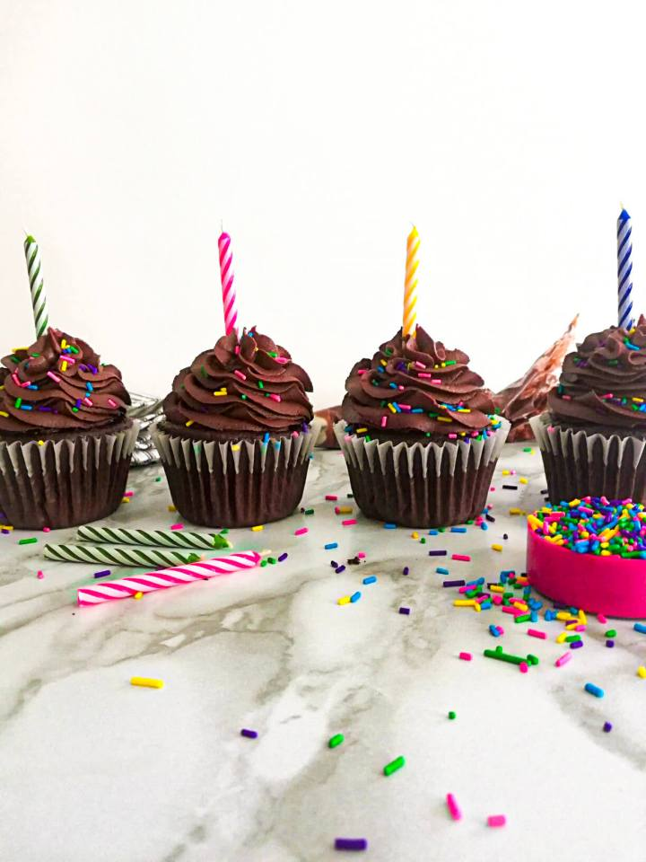 chocolate cupcakes frosted and topped with sprinkles with candles
