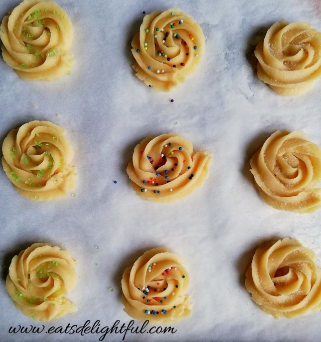 danish butter cookies on baking sheet with sugar and sprinkles