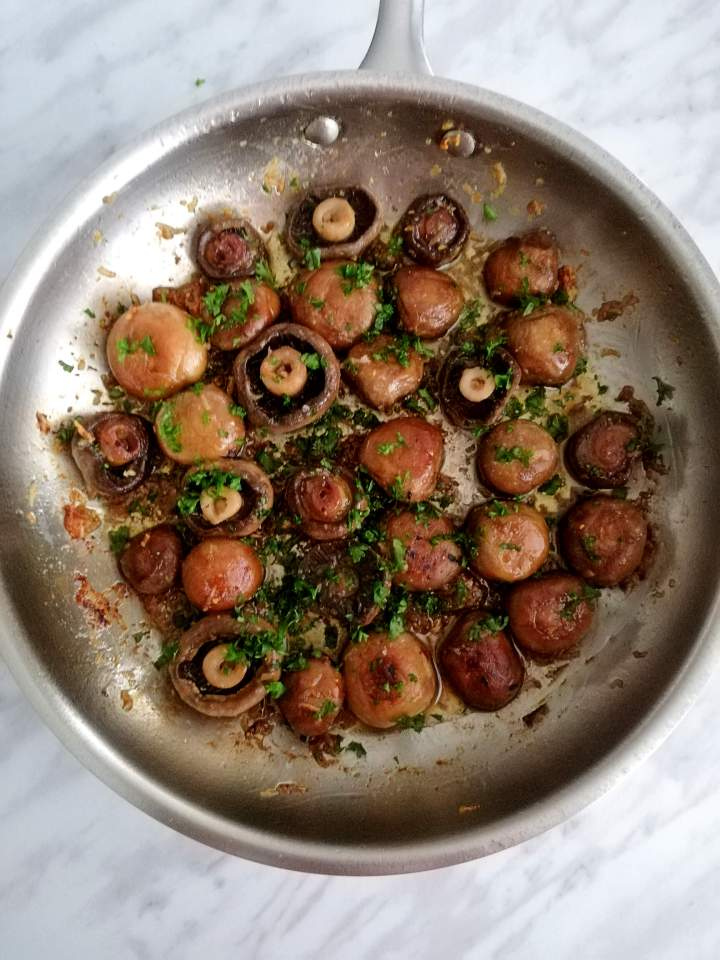 garlic butter mushrooms in skillet with parsley