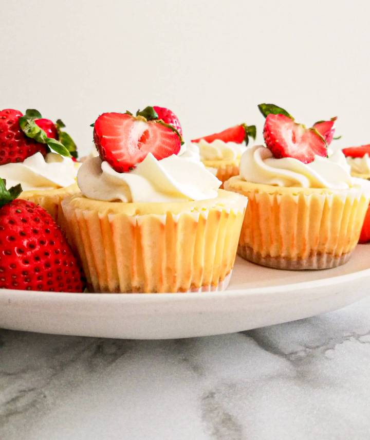 mini cheesecakes topped with whipped cream and strawberries 4