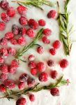 sugared cranberries and rosemary overhead on parchment paper (1)