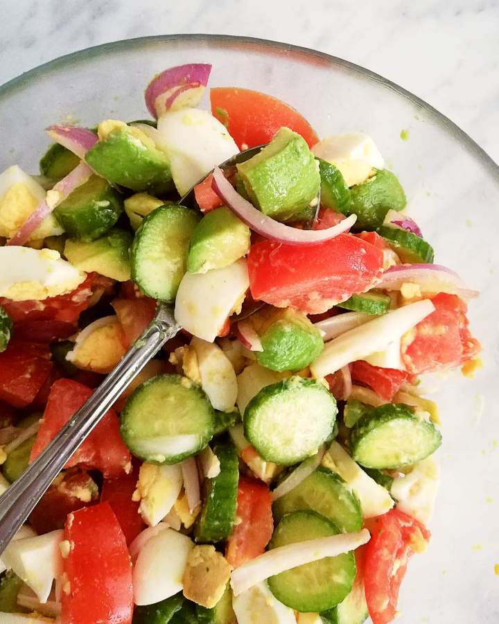 egg and avocado salad on spoon close up