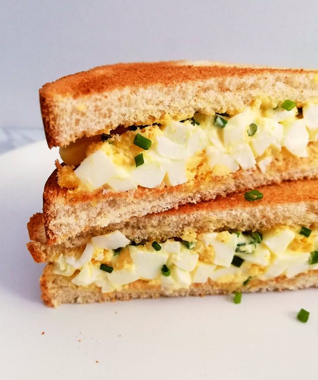 egg salad sandwich sliced in half and stacked close up left