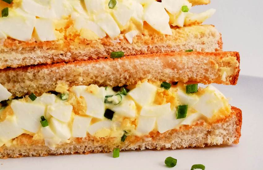 egg salad sandwich sliced in half and stacked close up right