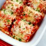 lasagna rolls baked and topped with parsley close up