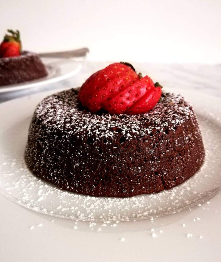 chocolate lava cake dusted with powdered sugar and topped with strawberries