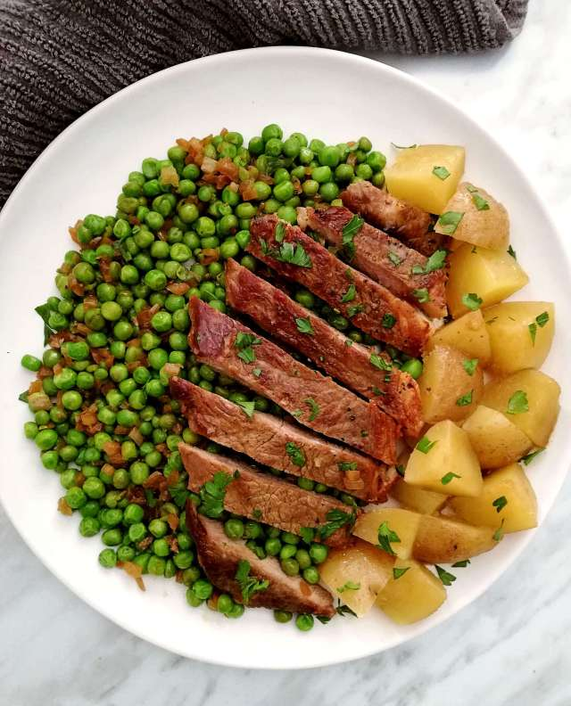 steak and peas with potatoes on side overhead