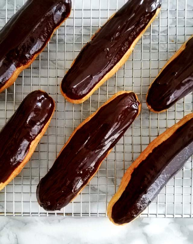 éclairs filled and dipped in chocolate on wire rack