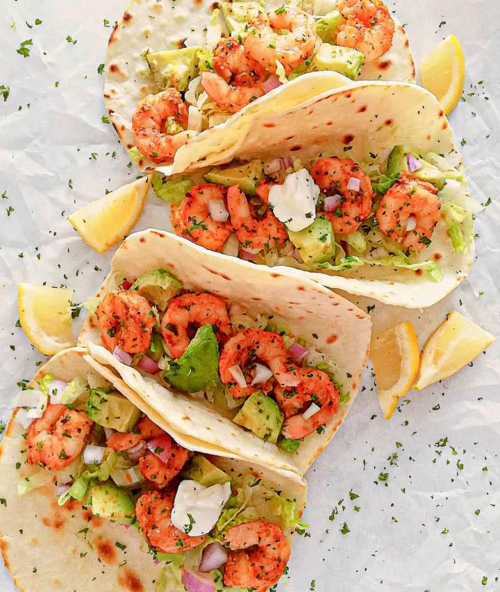 shrimp-tacos-with-lemon-wedges-and-parsley-lined-up-1