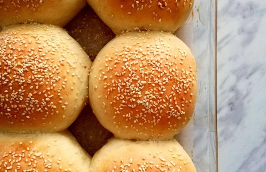 baked hamburger buns in baking dish close up overhead