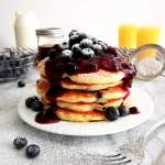 blueberry-pancakes-stacked-topped-with-blueberry-sauce-and-powdered-sugar