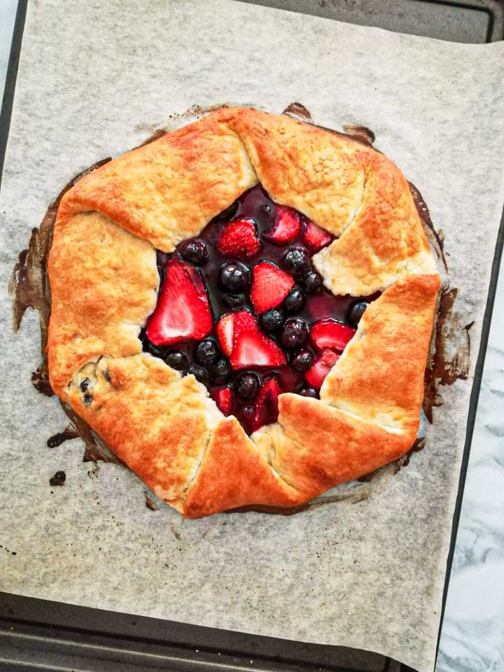 mixed berry galette baked on baking sheet