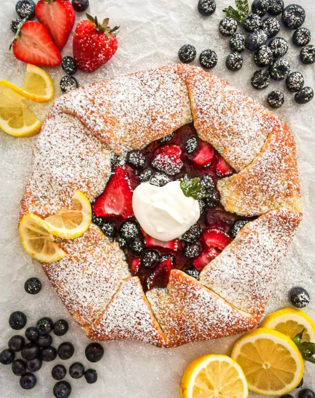 mixed berry galette topped with powdered sugar and whipped cream with blueberries, strawberries, and lemon garnishes on the sides