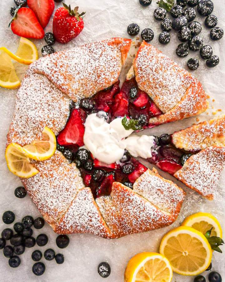 mixed berry galette topped with whipped cream and sliced