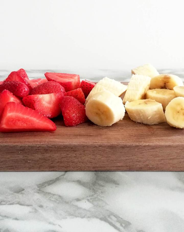 strawberry banana smoothie - sliced strawberries and bananas on cutting board