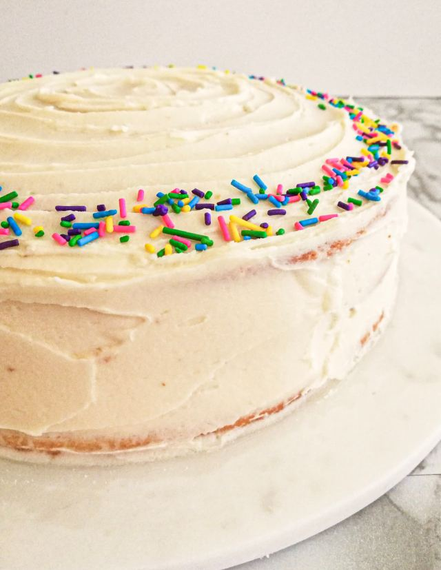 vanilla birthday cake without a cake pan frosted and topped with sprinkles