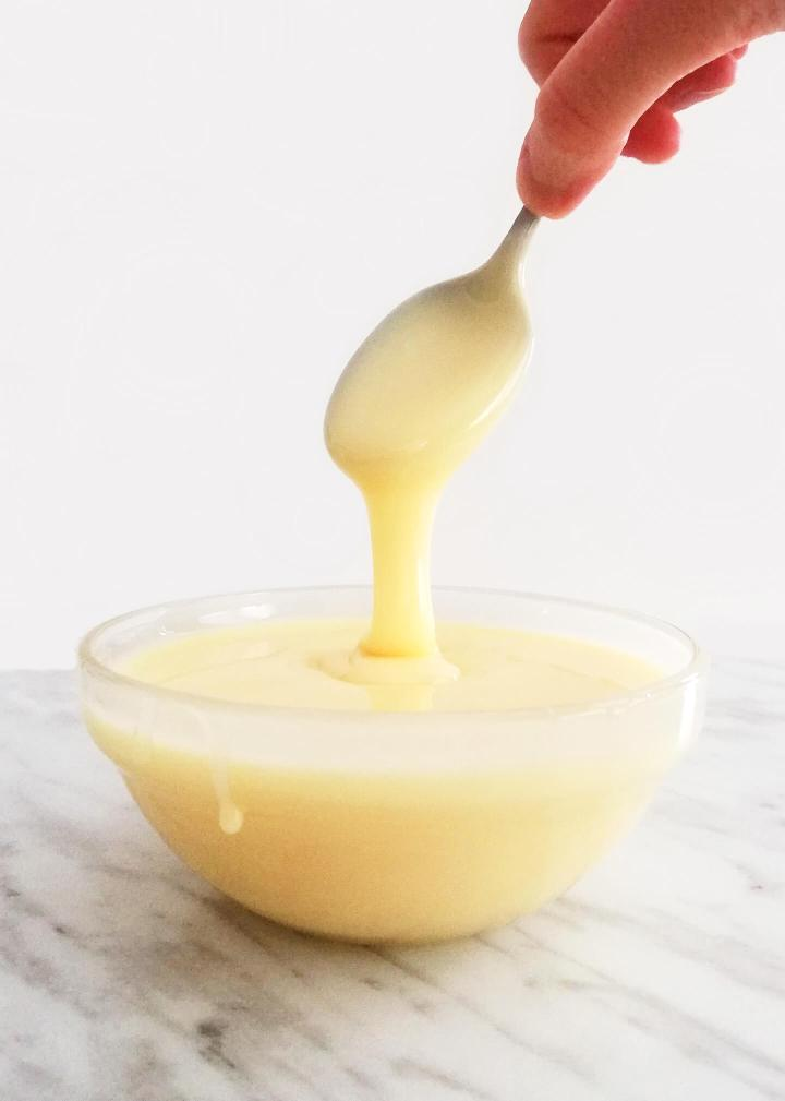 homemade sweetened condensed milk dripping condensed milk into bowl with spoon