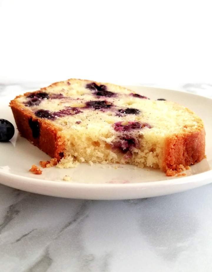 lemon blueberry quick bread slice in plate with piece missing