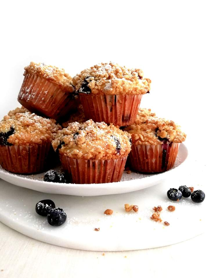 blueberry muffins with streusel topping dusted with powdered sugar in plate 1