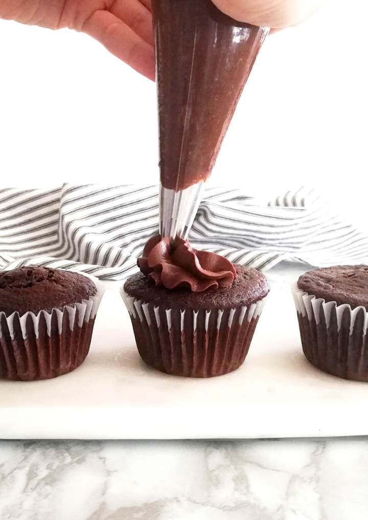 piping buttercream on cupcakes