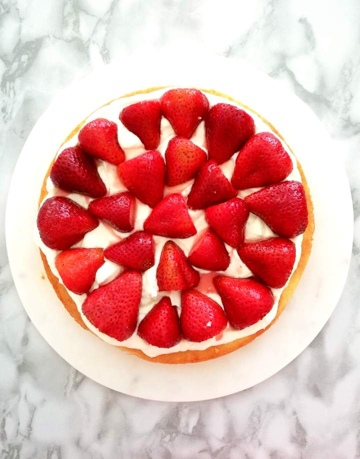 strawberry shortcake cake sponge cake topped with whipped cream and strawberries