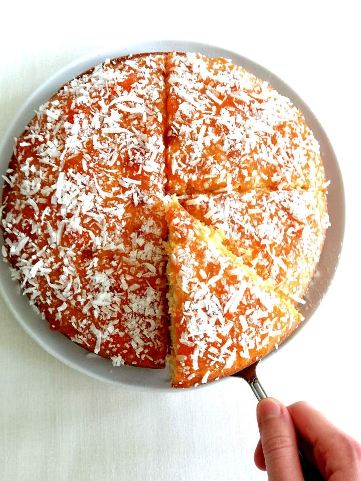 coconut jam cake lifting slice out of cake