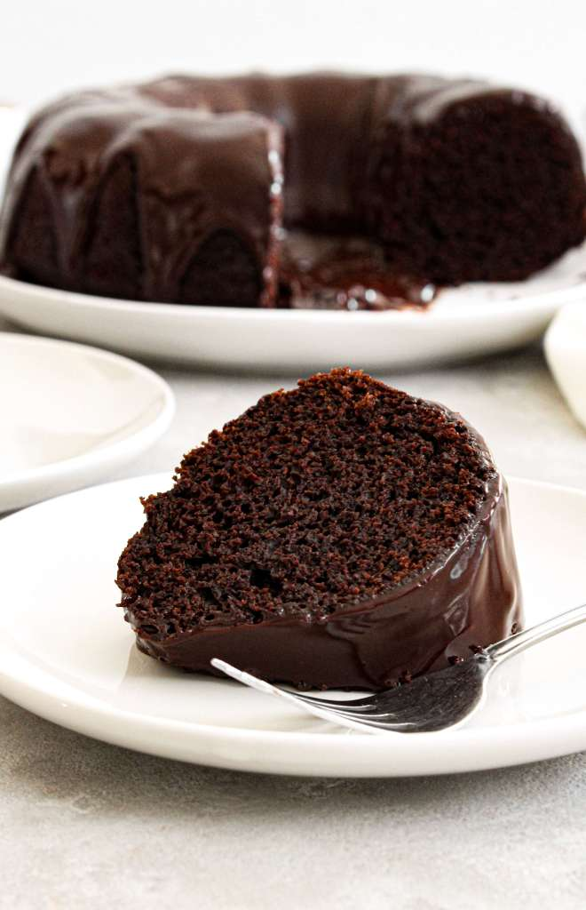 chocolate bundt cake topped with chocolate ganache slice in plate