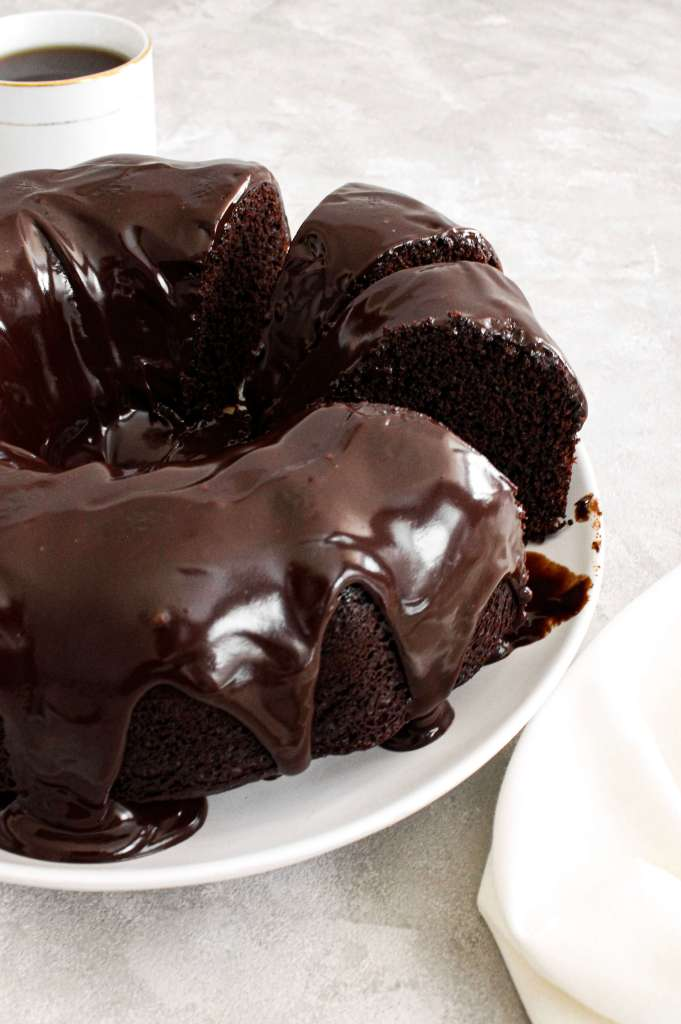 chocolate bundt cake topped with chocolate ganache sliced side view