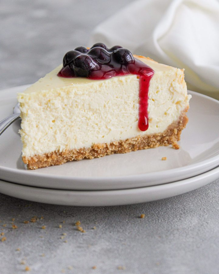 classic cheesecake slice in plate topped with blueberry sauce