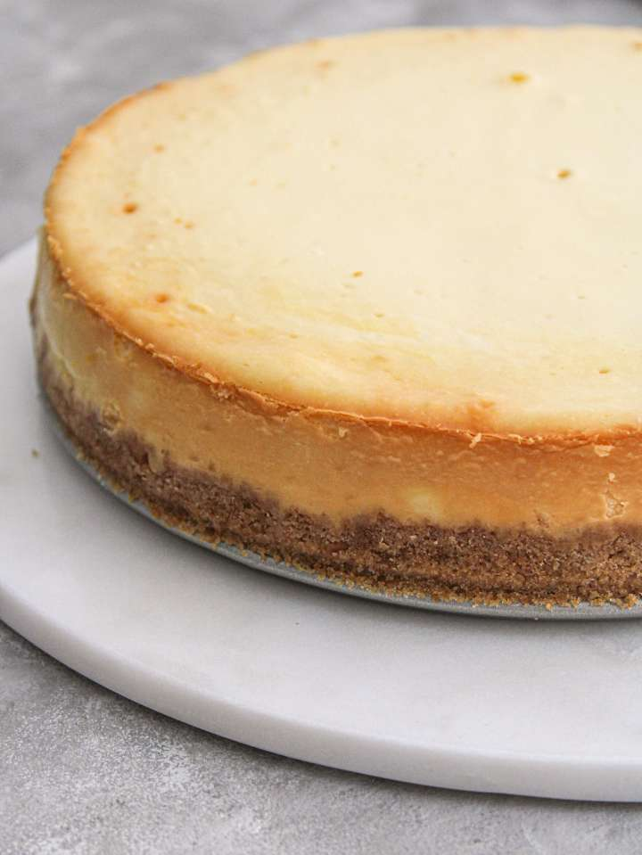 classic cheesecake on serving platter quarter view close up