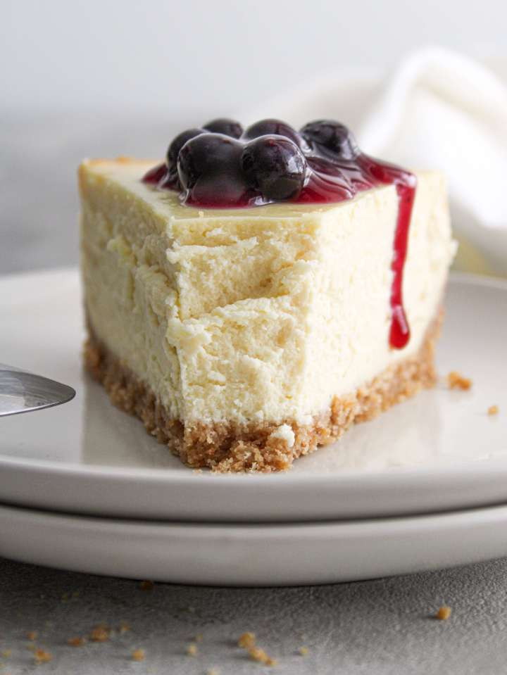 classic cheesecake topped with blueberry sauce slice in plate with piece missing