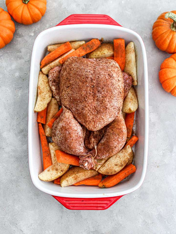 fall spice roasted chicken raw chicken in baking dish over bed of veggies