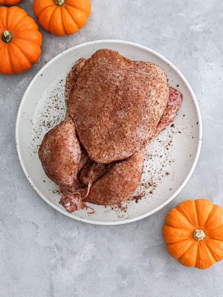 fall spice roasted chicken raw chicken in plate and seasoned