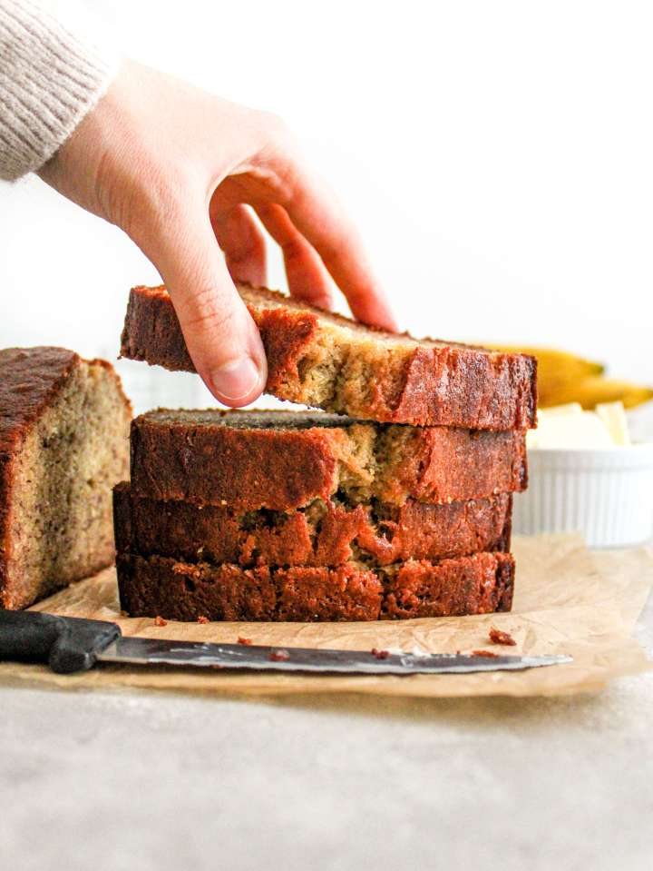 banana bread slices stacked with hand taking the top slice