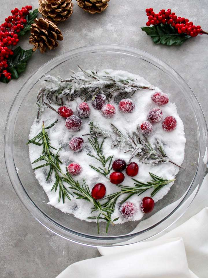 sugared cranberries and rosemary rolling in sugar